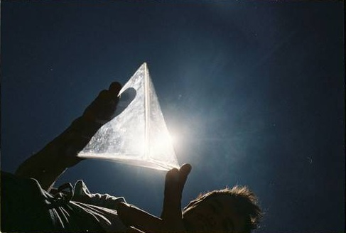 man holding glowing pyramid